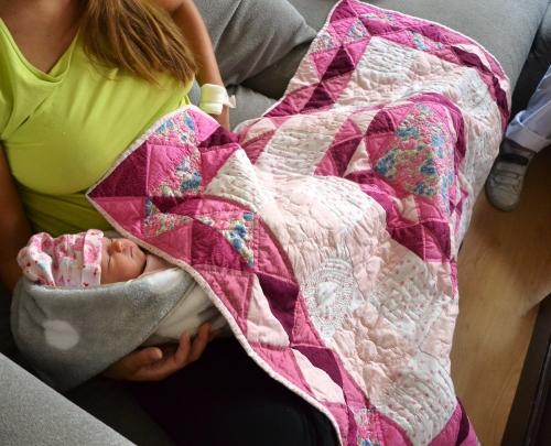 een roze meisje onder een roze quilt.....